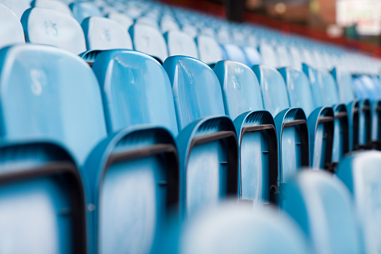row of empty blue bleacher seats